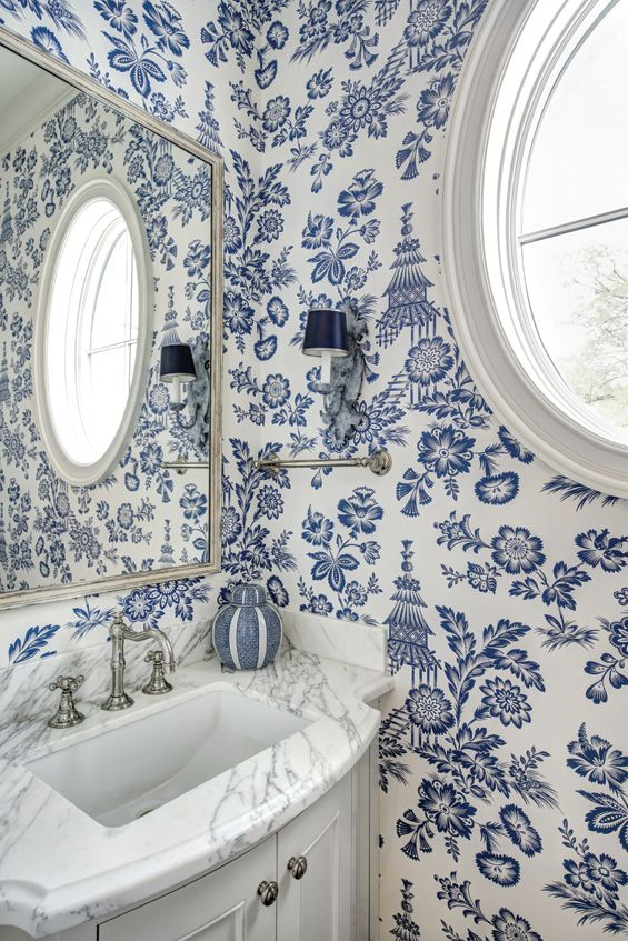 Playful chinoiserie toile wallpaper in the informal powder bathroom echoes the color scheme from the kitchen and breakfast area. Custom bow front sink basin is by Christina Graci Javanmardi. Fixtures are polished nickel; Custom mirror, painted lampshades and sconces.