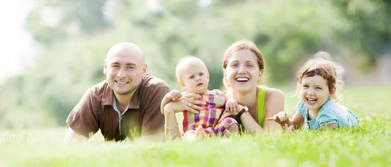 Happy family of four  at  grass in summer