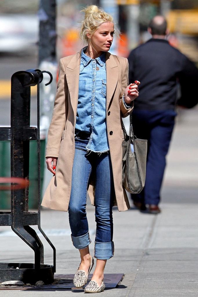 La actriz Amber Heard gana puntos cool al mezclar sus vaqueros tobilleros con slippers de tachuelas.     Su total look denim se complementa a la perfección con abrigo masculino y bolso Falabella de Stella McCartney.