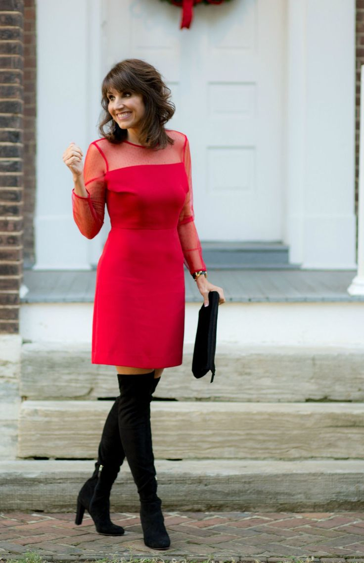 Cyndi Spivey wearing a pair of black suede thigh high boots paired with a red dress.