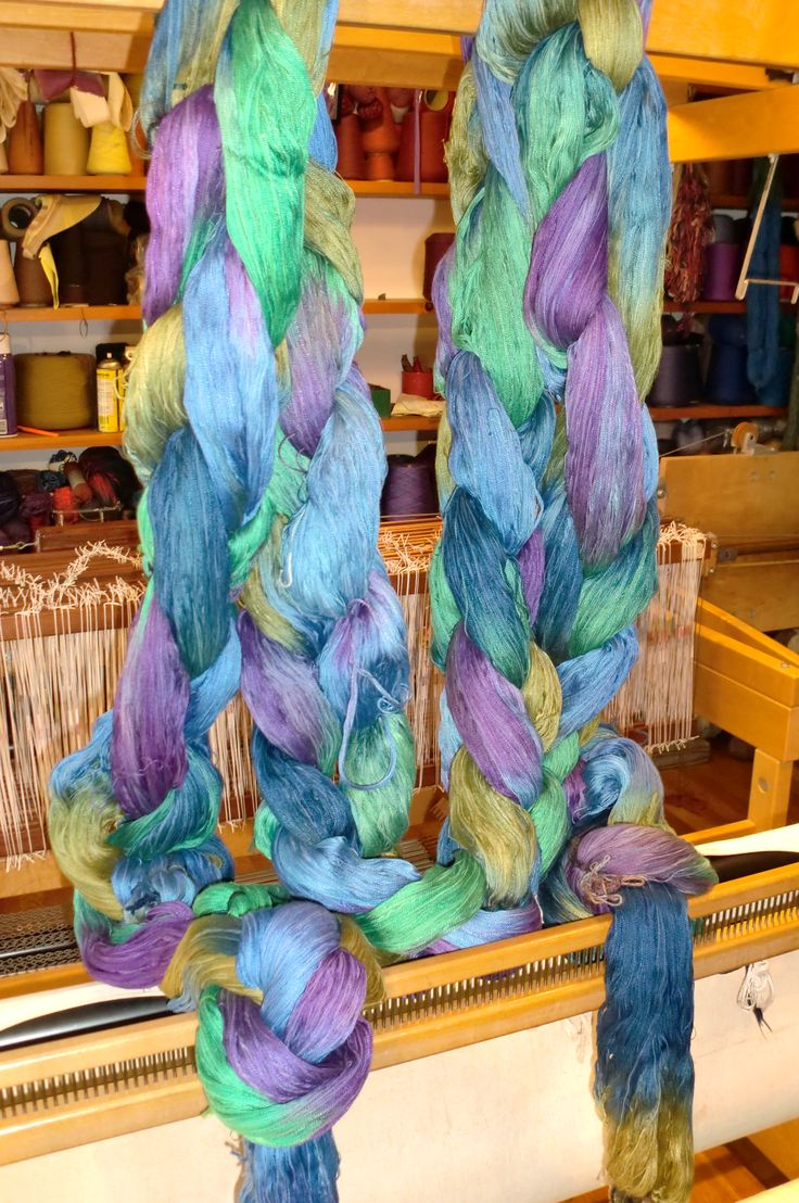 """Space-dyed warp by Caroline Hicks-Ellwood, made for Sandy Lommen.  The warp is cotton, 20 yards long and 62"""" wide.  Chained warp is hanging off the back of Sandy's AVL loom during the warping process."""