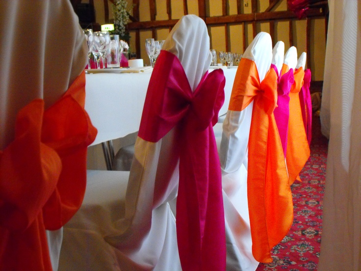 Alternating Orange and Fuschia Satin Bows on White Chair Covers