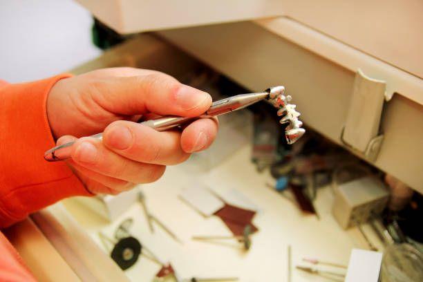 hands is holding a steel metal dental crown dental prosthesis work