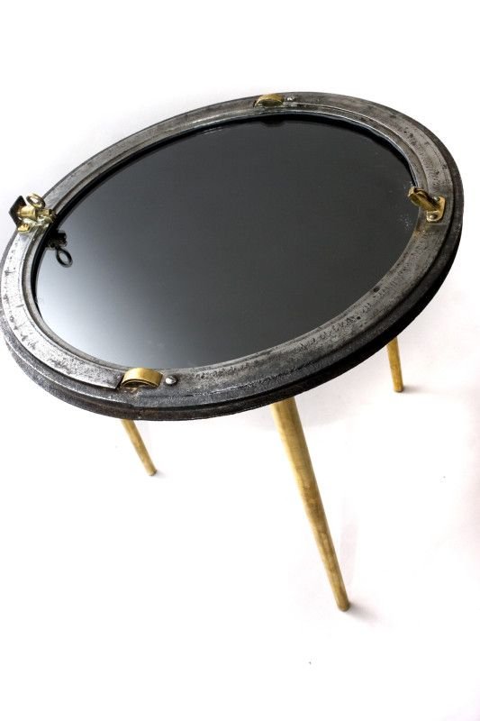 An old porthole window is REused as a contemporary side table with custom made tapered solid brass legs and a smokey grey mirror top