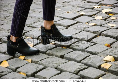 Closeup of young woman legs on Parisian cobblestone street covered with yellow autumn leaves. - stock photo