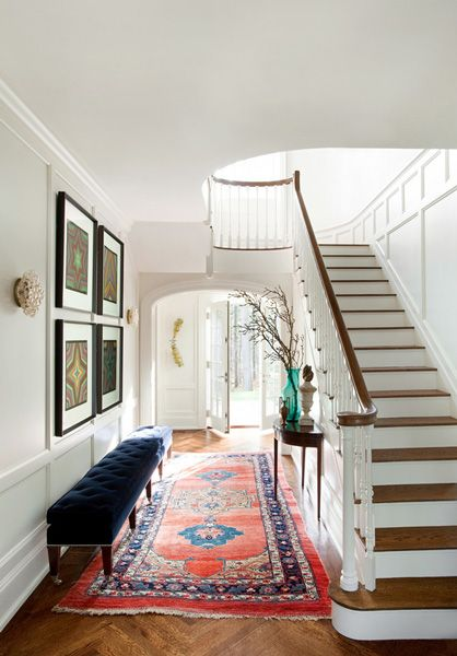 "Designer Frank Roop used an oversize tufted bench to add an ""unexpected or dramatic"" element to the entryway of this Boston-area colonial home."