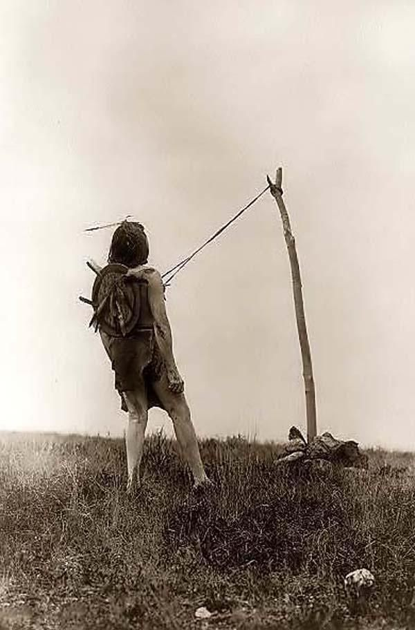 This is a rare photograph of the Native American Piercing Ritual, a rite of manhood among the Indians. It was created in 1908 by Edward S. CurtisThe photograph illustrates a Crow man, leaning back slightly, with strips of leather attached to his chest by sticks pierced through his breast. He is tethered to a pole that is secured by rocks. This is all part of the piercing ritual of the sun dance.