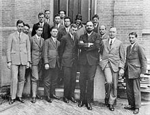 Fifteen men in suits, and one womyn, pose for a group photograph Heike Kamerlingh Onnes' Laboratory in Leiden, Netherlands, 1926. Oppenheimer is in the second row, third from the left.