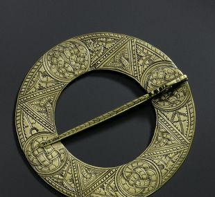 Circular plaid brooch of brass with one face decorated with roundels containing interlace alternating with triangles filled with triquetras
