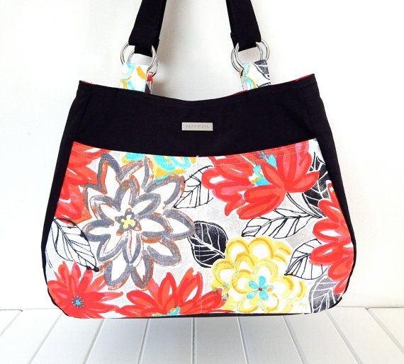 This vibrant bag has been hand made using a black cotton drill fabric contrasted with a gorgeous floral Waverly designer fabric. It would make a stylish, eye catching accessory for that special occasion or to use as an every day tote style bag with plenty of room for all the essentials. The floral panel on the front is also a large double slip pocket.  The outer fabric is a medium weight fabric that has been interfaced and fleeced for extra body and shape. It has an internal single pocket…