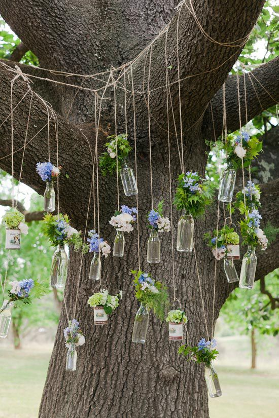 Photography by Kate Robinson, Australia. This is the altar backdrop for an outdoor wedding. I like the idea of bottles of flowers suspended by twine.