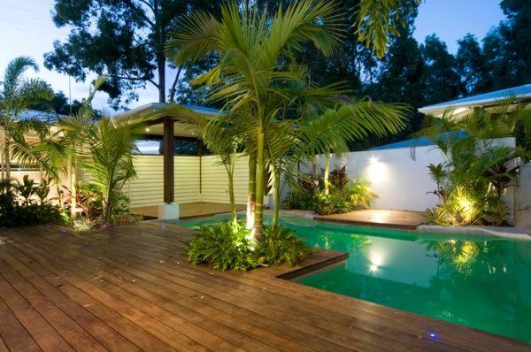 terrasse en bois ou composite, jolie piscine dans un jardin tropical