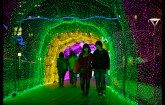 A young couple walk through a tunnel of LED lights during a Christmas illumination event at the Tokyo Dome City Attractions amusement park.
