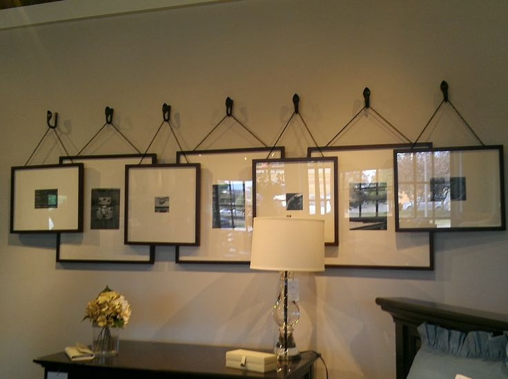 Gallery wall, overlapping frames hung on hooks.