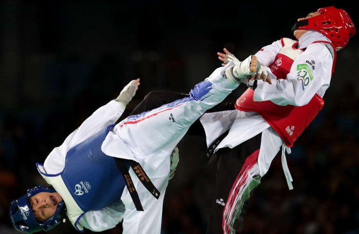 Phannapa Harnsujin (THA), blue, and Kimia Alizadeh Zenoorin (IRI) compete in a women's taekwondo 57kg repechage match at Carioca Arena 3 during the Rio 2016 Summer Olympic Games.