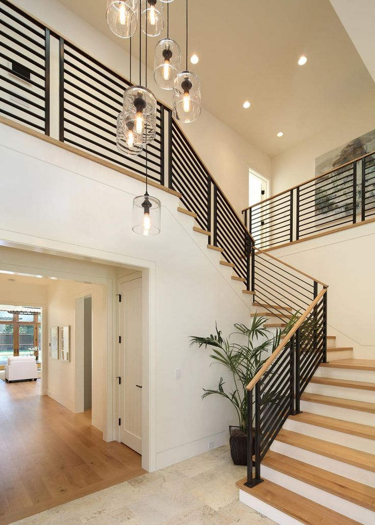 This sleek staircase pairs light hardwood steps with a black metal railing for a high contrast look. Glass pendant lights hang at varying lengths from the ceiling.