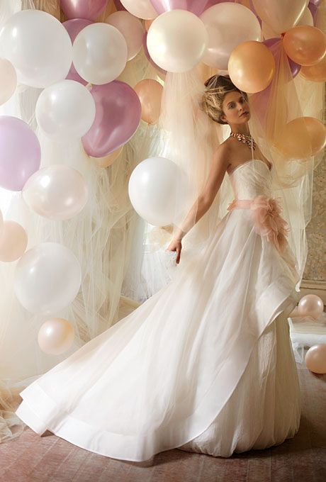 Brides.com: . The highlights of this silk-organza-and-tulle confection include a draped sweetheart bodice trimmed with fringe, a mohair peplum skirt, and a blush-colored flower belt. Gown, $5,350, Rivini. Necklace, House of Lavande Vintage Weiss.
