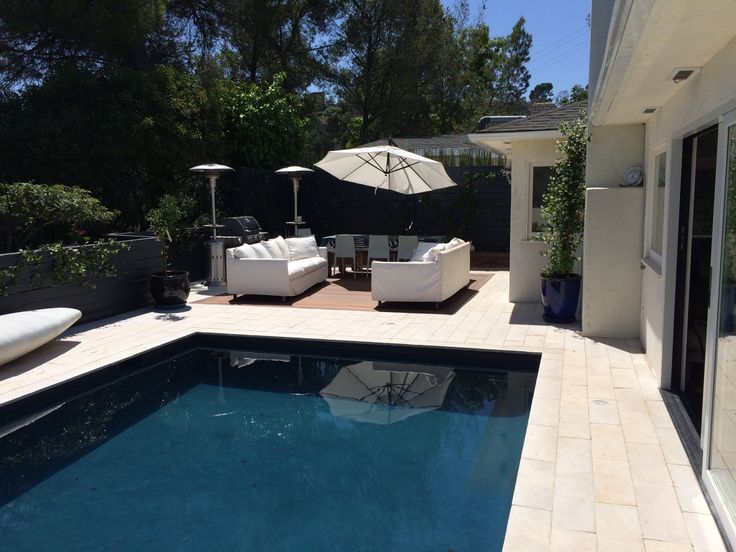 To add to the astonishing view of the Hollywood Hills, this backyard combines the beautiful Epay wood deck, with the Sandstone tile and midnight gray plaster to bring elegance and charm to the house.
