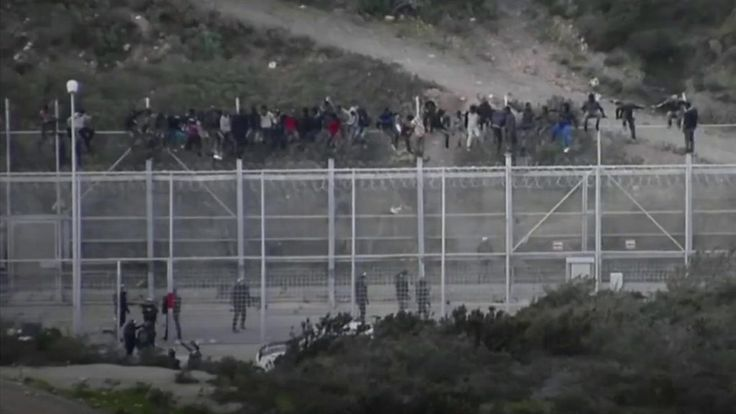 migrants storm spanish border fence border enclave ceuta on border wall id=20853