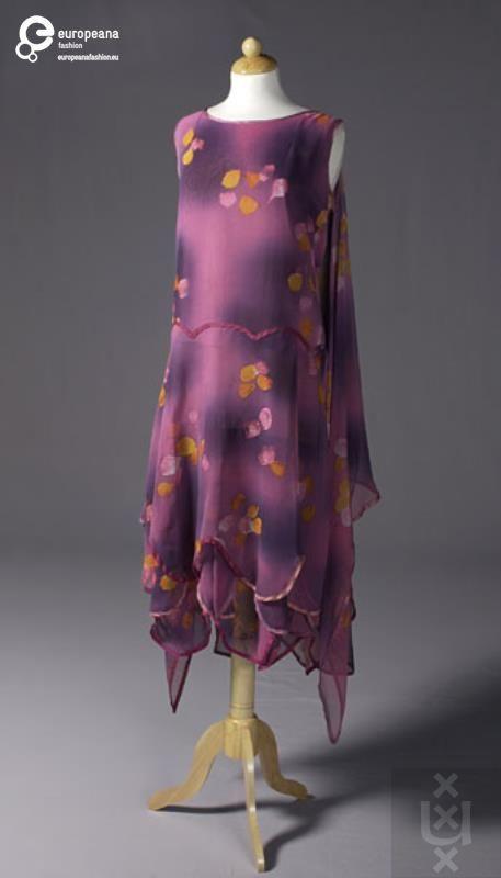 Een paars/rose jurk van synthetische voile, bedrukt met oranje/gelige bladeren. De jurk is uit verschillende lagen opgebouwd en bevat een lage taille (twintiger jaren). Alle randen en zomen zijn afgebiesd met paars satijn biaiband.
