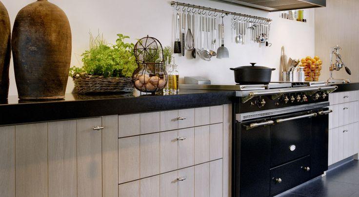 In deze prachtige, luxe keuken is het fornuis een pronkstuk. Want zoals de open haard hier bijna in de keuken staat, zo staat het fornuis bijna in de kamer. Dat is wel zo leuk voor de kok van de avond.