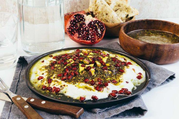 Recept voor labneh dip voor 4 personen. Met zout, olijfolie, peper, yoghurt, pistachenoten, bruin brood, munt, zwarte olijven, za'atar, granaatappel en chilivlokken