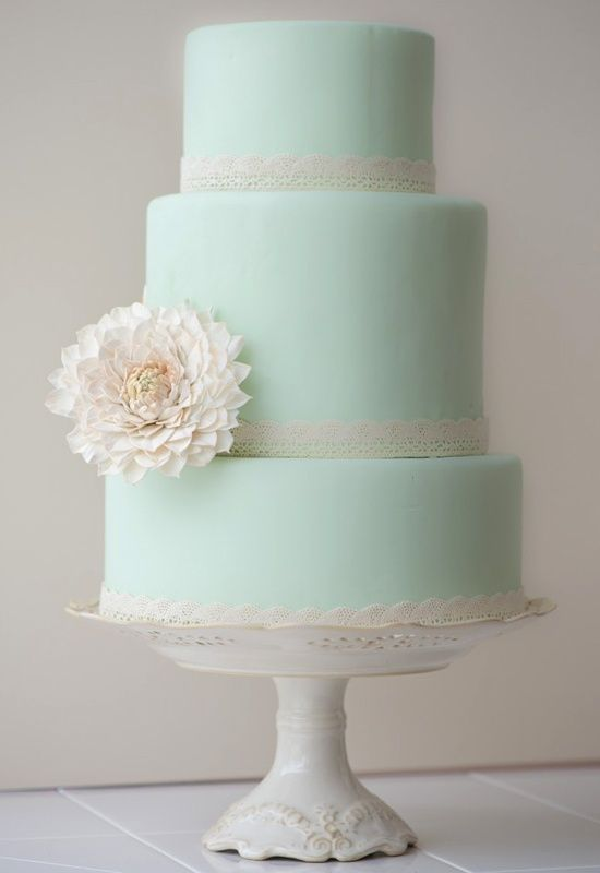 Going with a pastel colored cake is a way to infuse color, but keep it a neutral. In this mint  colored cake, the design is kept simple with a single flower for accent.