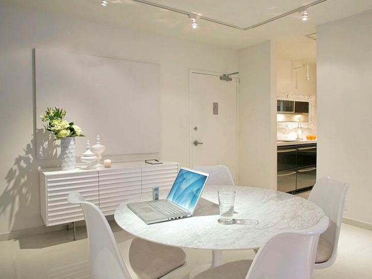 An all-white color palette and sleek furniture are normally a nod to modern design, but the addition of fresh flowers and minimalist furnishings gives this space more of a simple beach look. The crisp color palette continues into the kitchen for a unified look. Design by Andreas Charalambous
