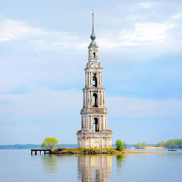 Bell Tower of Saint Nicholas Church - Kalyazin, Russia - The entire area surrounding it was flooded by Stalin in the 1930s to make way for the Uglich reservoir. Now, only the bell tower of one cathedral remains, jutting up from the water like a lighthouse, and a small area of land surrounds it for small boats to dock. Even though most of the building has been submerged, the spire still stands 244 feet above the water.