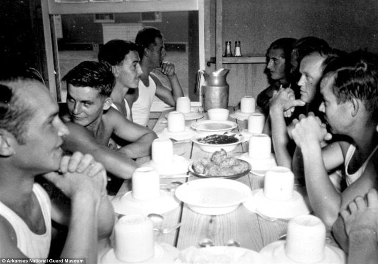 Some of the German POWs at a camp in the U.S. gather round a table to eat together. In the camps they were provided with hot food and warm water