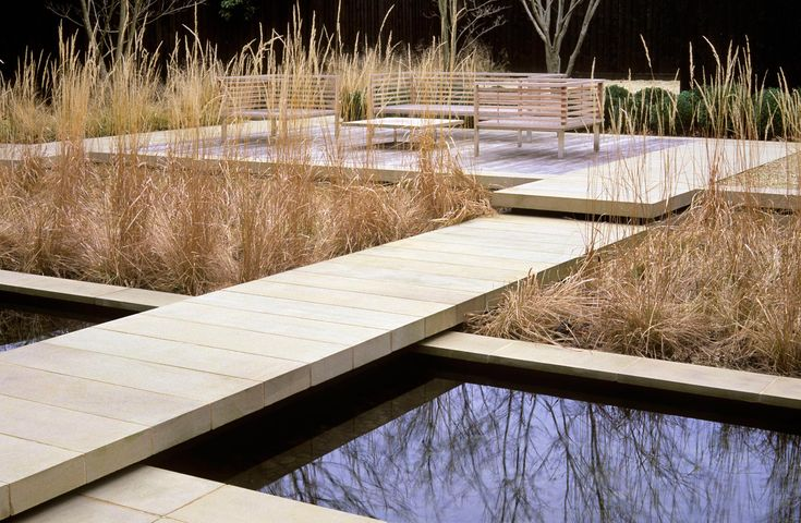 pale stone walkway over rill with honey tones of grasses to a patio/seating area - Annie Pearce   London