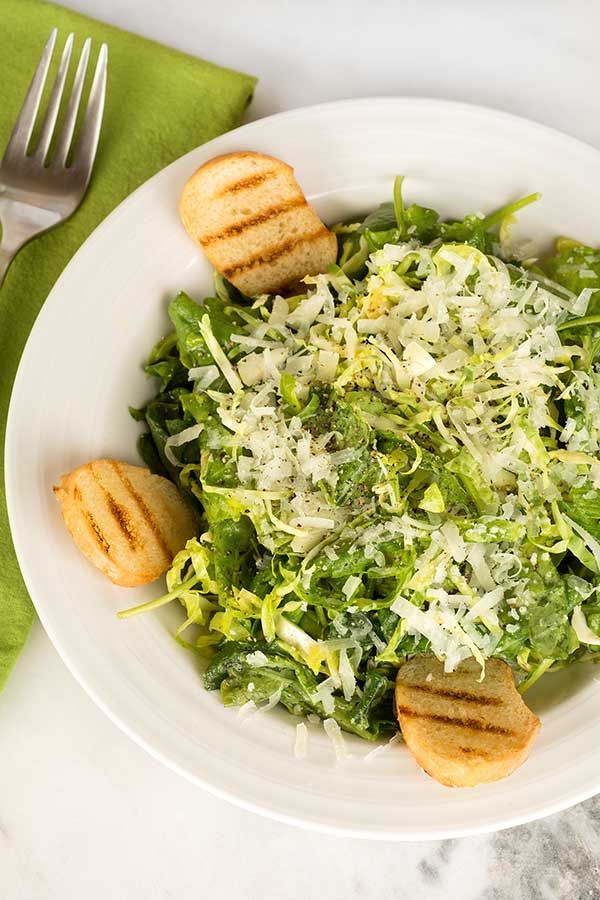 Brussels Sprouts and Kale Caesar Salad: A great side to serve with grilled steaks, chops or chicken, this tasty twist on a classic Caesar salad is made with fresh brussels sprouts and baby kale.