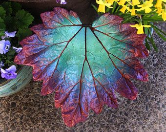 This leaf would make an attractive accent to any garden. Painted in colors reminiscent of a tropical island, it would look lovely among all garden color palettes. Here it has been photographed sitting atop of a patio table in the garden. Place it with perennials as they finish flowering to continue the pop of color long after the blooms have faded. This casting has a drain hole in the bottom. This leaf would also make a great eye catching piece indoors on the coffee table or in a bathroom…