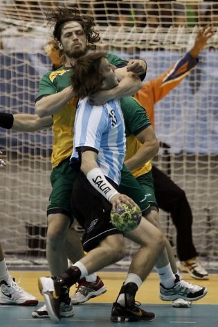 Brazil's Fabio Chiuffa, back, grabs Argentina's Juan Fernandez during the men's handball gold medal match at the Pan American Games in Guadalajara, Mexico, Monday, Oct. 24, 2011. (AP Photo/Eduardo Verdugo) Photo: Eduardo Verdugo, AP
