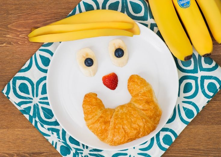 Kid-friendly breakfast with bananas & blueberry eyes, mango hair, strawberry nose and a croissant smile!