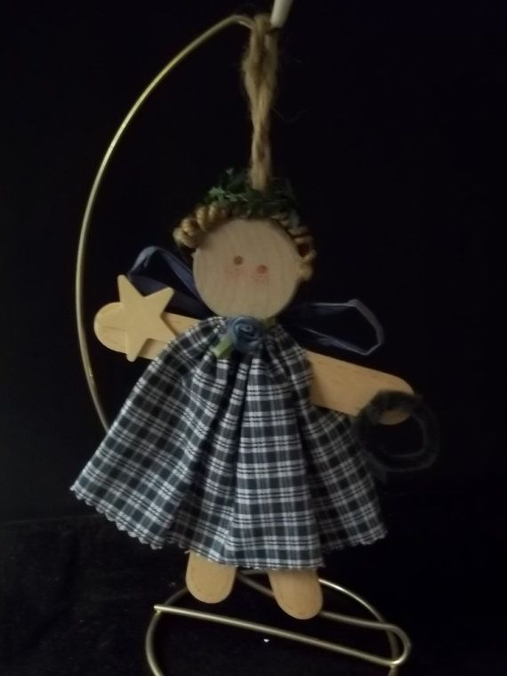 This cute angel is made from large wooden craft sticks. Her dress is made of calico her hair is curly jute. A paper raffia bow for wings and holly leaves for her halo. Measures 6- not including hanger.