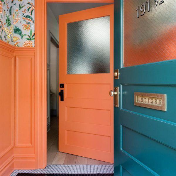 O hall de entrada, em laranja com tapete em pastilhas, recebe papel de parede Osborne & Little estampado. Charme puro!
