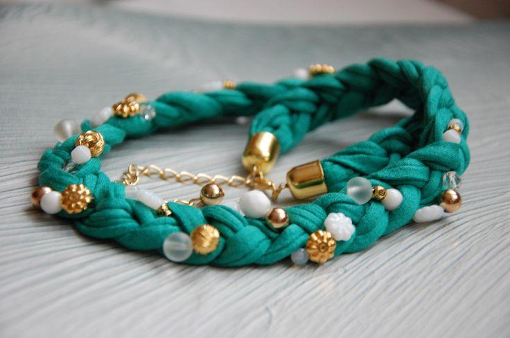 Tyrkysový Nápadný náhrdelník vyrobený z textilie zapletené do copánku a skleněných a kovových korálků. Komponenty a zapínání v barvě zlaté.