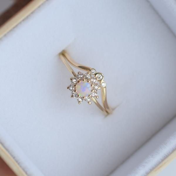 """-solid 14kt gold -4mm natural Australian opal -1.7mm white sapphires This delicate yet striking ring is a mesmerizing little ring. It's name is relevant to its design and translates to """"the flower of"""