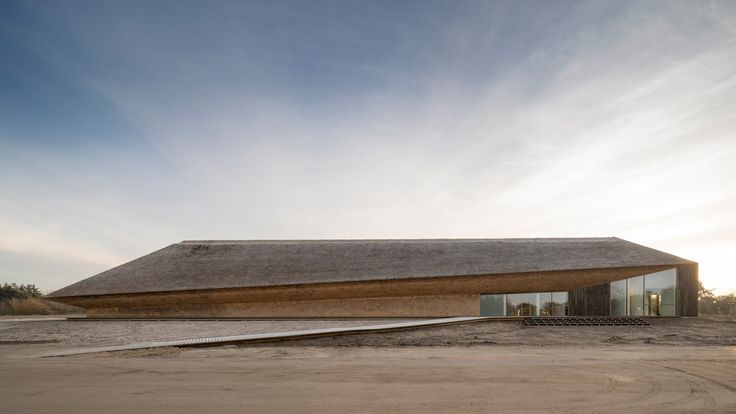 Dorte Mandrup Arkitekter paired thatch with blackened wood for this extension to a visitor's centre on the Wadden Sea mud flats in Denmark