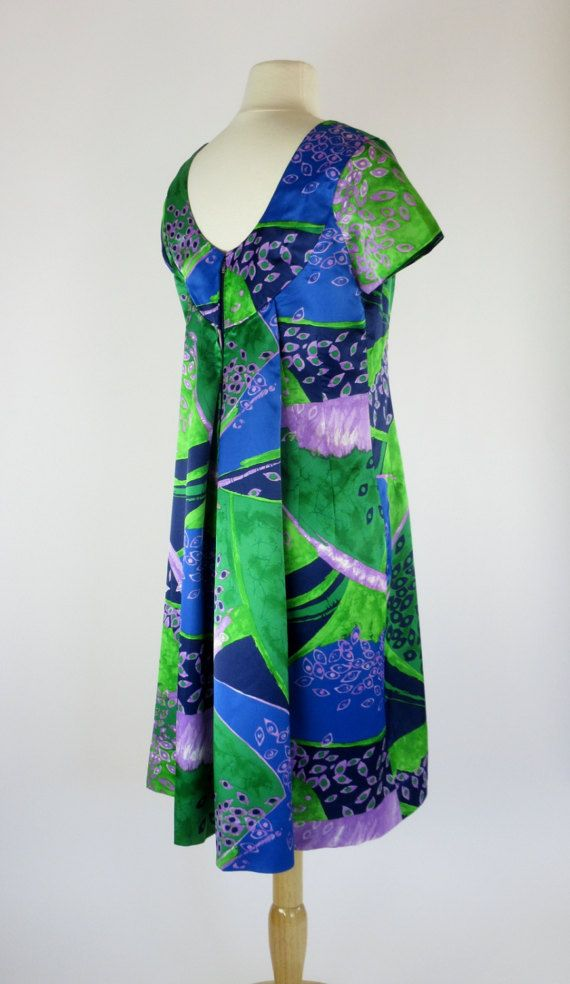 This beautifully detailed Hawaiian-style dress was made in the British Crown Colony of Hong Kong circa 1963.    The dress is made from medium weight polyester sateen in a bold abstract design of peacock green, marine blue, and lavender accents.