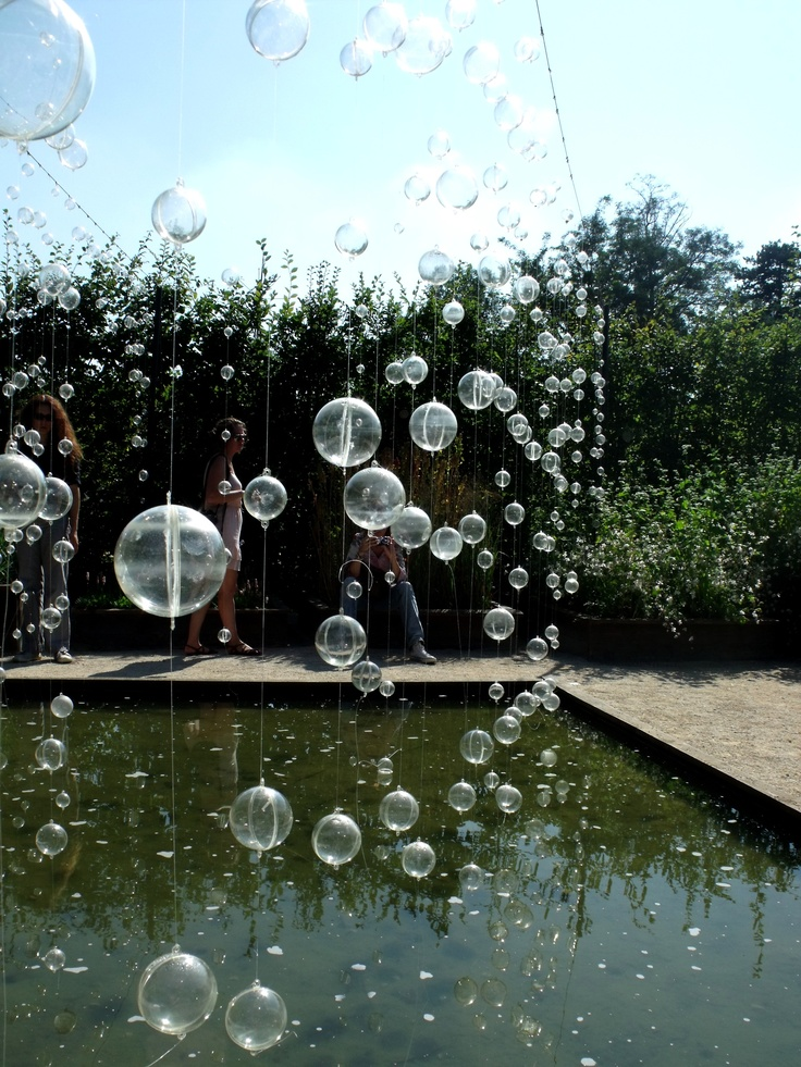Jardin de Chaumont- clear plastic Christmas ornaments hung from fish line over the pool/pond
