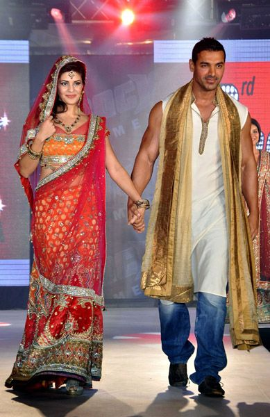 Indian Bollywood film actors John Abraham (R) and Jacqueline Fernandez walk the ramp wearing creations by designer Aki Narula during the promotion of their upcoming Hindi film 'Housfull 2' in Mumbai late.
