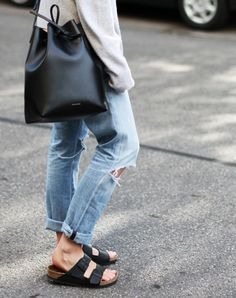 Ripped jeans, Birkenstocks, and bucket bag.
