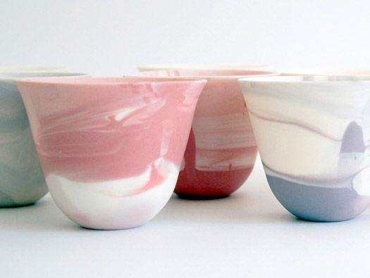 ceramic cups with a colourful swirl pattern created by using the slip-casting…