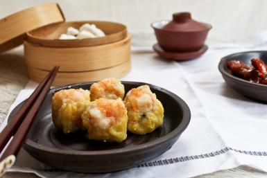 Chinese dim sum spread with classic prawn dumplings (siu mai) and steamed barbeque pork buns (Char siu bao) shown with Chinese tea. - Jen Voo Photography/Moment/Getty Images