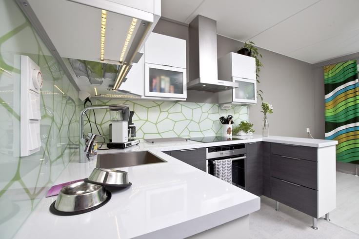 Tapetilla saa välitilasta hyvin persoonallisen. Oheisessa keittiössä tapettia suojaa lasi koko välitilan matkalta. Tasomateriaalina on käytetty valkoista laminaattia, joka on kestosuosikki hyvän kestävyytensä ja tyylikkyytensä ansiosta.