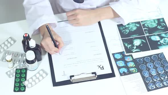 Doctor Fills Out Medical Prescription Forms Using X Rays