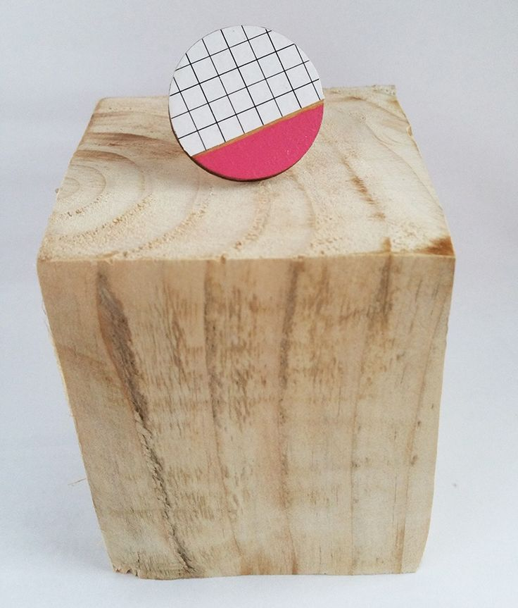 Plywood is cut into a clean, simple circular shape to create a ring with understated elegance.The wooden circular ring sits on a silver plated adjustable ring bed.One side of it features a simple grid print