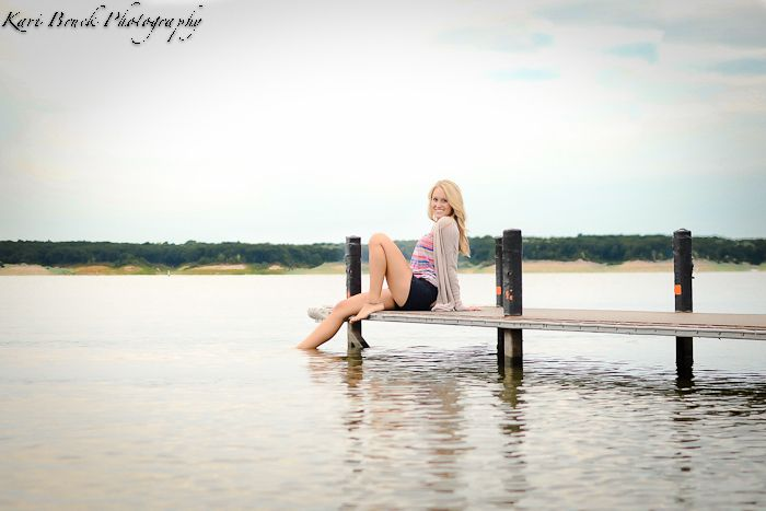 2014 High School Senior girl for posing picture ideas. Senior girl sitting on a dock on a lake at sunset. High school senior session pose inspiration for senior pictures.